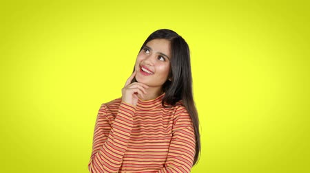 soñar despierto : Attractive young woman with long hair, daydreaming in the studio while smiling and looking up. Shot in 4k resolution with yellow background
