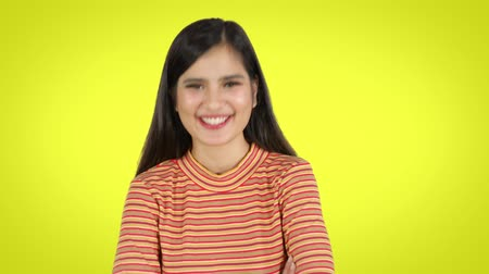 nevetséges : Cheerful young woman looking at the camera and laughing in the studio. Shot in 4k resolution with yellow background