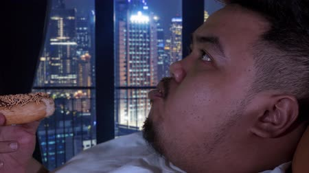voracious : Closeup of obese man enjoying donuts while relaxing in apartment. Shot in 4k resolution