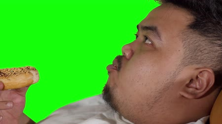 voracious : Closeup of overweight man eating donuts in the studio. Shot in 4k resolution with green screen background Stock Footage