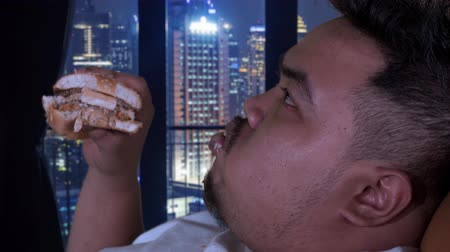 voracious : Closeup of overweight man enjoying hamburger while relaxing in the apartment. Shot in 4k resolution Stock Footage
