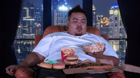 жадный : Greedy fat man enjoying popcorn and others junk foods while sitting on sofa in apartment. Shot in 4k resolution Стоковые видеозаписи