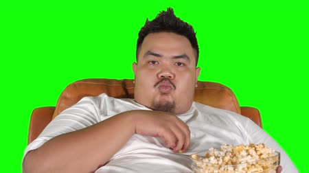 жадный : Fat man enjoying popcorn while sitting on the sofa and watching TV. Shot in 4k resolution with green screen background Стоковые видеозаписи