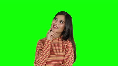 schermen : Happy young woman daydreaming in the studio while smiling and looking up. Shot in 4k resolution with green screen background Stockvideo