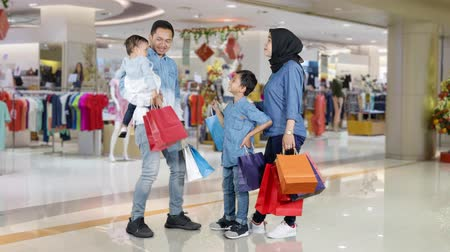 モール : Happy muslim family holding shopping bags while standing in the shopping center. Shot in 4k resolution 動画素材