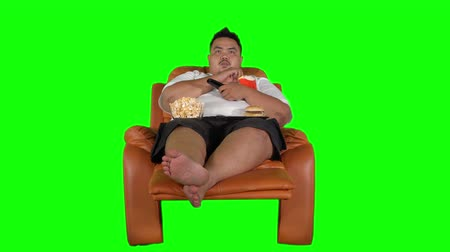 ganancioso : Overweight man relaxing on the sofa while eating junk foods and watching TV. Shot in 4k resolution with green screen background