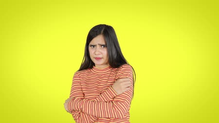 paquistão : Scared young woman looking at the camera while standing in the studio. Shot in 4k resolution with yellow background