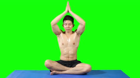 meditující : Young muscular man doing yoga and meditating while sitting on a yoga mat. Shot in 4k resolution with green screen background