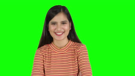 nevetséges : Funny young woman laughing at the camera in the studio. Shot in 4k resolution with green screen background