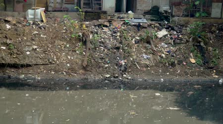 szárítókötél : JAKARTA, Indonesia - May 08, 2019: Polluted river and slum houses with dirty plastic waste Stock mozgókép