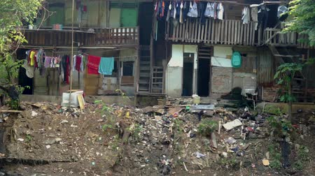 bídný : JAKARTA, Indonesia - May 08, 2019: Slum houses on the dirty riverside with plastic waste and other garbage