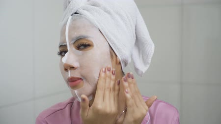 ovmak : Attractive young woman scrubbing facial mask on her face while looking on camera at home. Shot in 4k resolution Stok Video