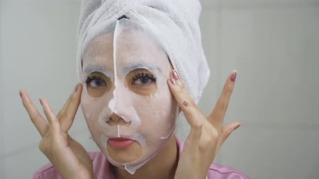 лицевой : Beautiful young woman applying facial mask while looking at camera in bathroom. Shot in 4k resolution Стоковые видеозаписи