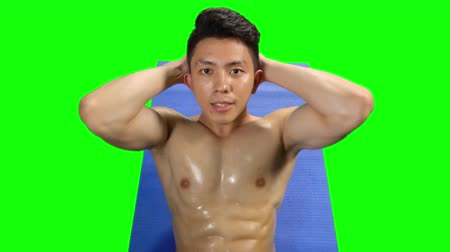 chroupat : Closeup of young handsome man with muscular body doing sit up on the mat. Shot in 4k resolution with green screen background Dostupné videozáznamy