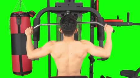 contra : Back view of young muscular man exercising on fitness machine. Shot in 4k resolution with green screen background Stock Footage