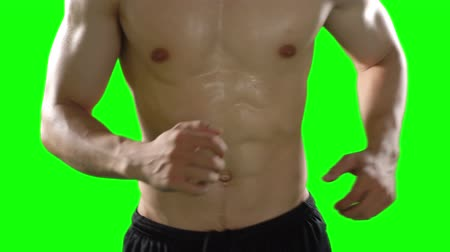 kaslı : Unknown muscular man doing exercise by running in place. Shot in 4k resolution with green screen background Stok Video