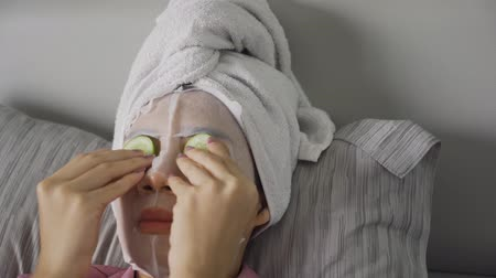 pepino : Young woman with facial mask covering eyes use cucumber slices and sleeping on the bed with a towel on head. Shot in 4k resolution