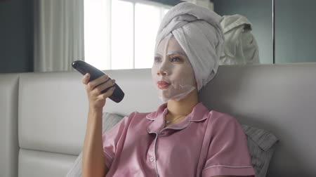 tv channel : Attractive young woman wearing facial mask treatment and watching TV on the bedroom. Shot in 4k resolution