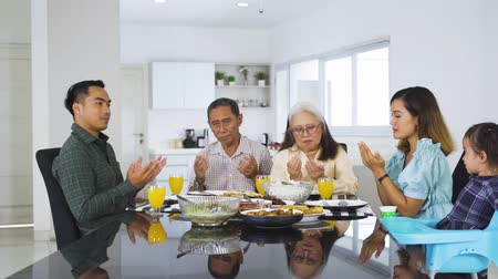 ислам : Happy three generation muslim family praying together before lunch in dinning room at home. Shot in 4k resolution
