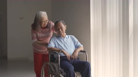 doente : Happy elderly woman chatting with her husband while sitting on wheelchair after recovering from stroke disease at home. Shot in 4k resolution Stock Footage