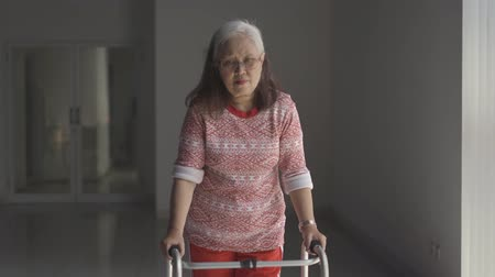 eski : Senior woman walking with a walker after recovering from stroke disease at home. Shot in 4k resolution Stok Video
