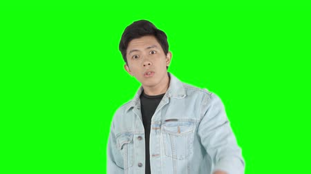 kaba : Angry young man looking and pointing at the camera emotionally in the studio. Shot in 4k resolution with green screen background Stok Video