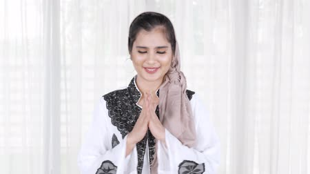 perdão : Attractive young Asian muslim woman smiling at the camera and showing a greeting gesture at home. Shot in 4k resolution