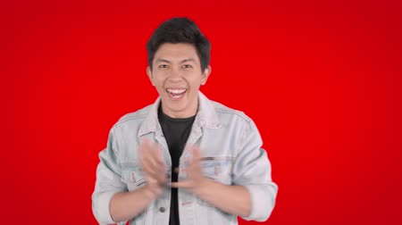 údiv : Cheerful young man looks surprised in the studio. Shot in 4k resolution with red background