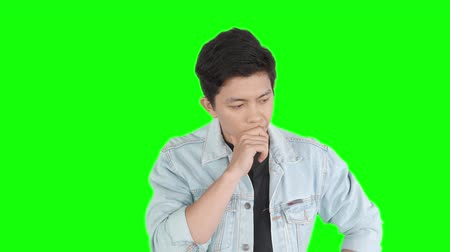 çözmek : Confused young handsome man standing in the studio while thinking and looks having an idea. Shot in 4k resolution with green screen background Stok Video