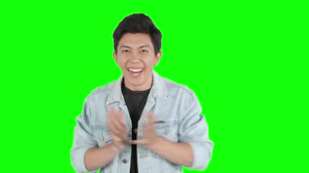 étonnement : Happy young man looks surprised and celebrating his success in the studio. Shot in 4k resolution with green screen background