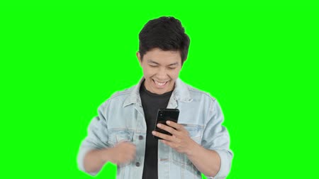 ler : Cheerful young handsome man reading a good news on his mobile phone while expressing his success. Shot in 4k resolution with green screen background