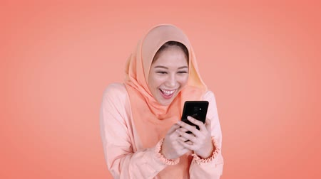 解決 : Pretty young Asian muslim woman looks shocked and happy while holding her smartphone in the studio. Shot in 4k resolution