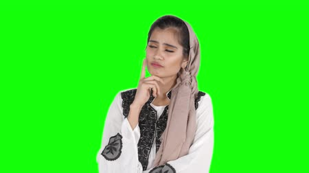 çözme : Pretty young muslim woman in headscarf standing in the studio while thinking and looks having idea. Shot in 4k resolution with green screen background