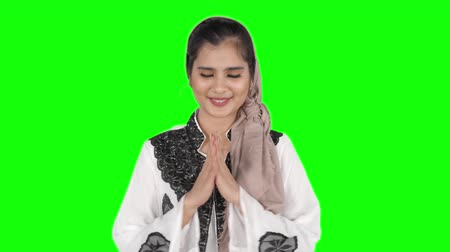 perdão : Pretty young Asian muslim woman showing a greeting gesture in the studio. Shot in 4k resolution