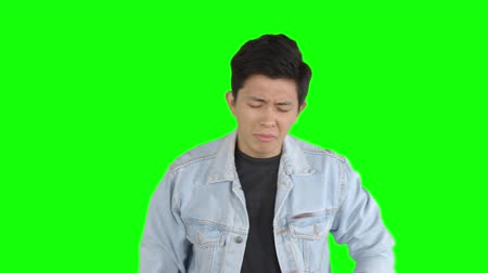 unlucky : Unhappy handsome young man standing in the studio with casual clothes. Shot in 4k resolution with green screen background