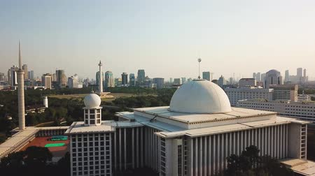 národní památka : JAKARTA, Indonesia - May 14, 2019: Aerial view of Istiqlal Mosque with white dome and Monument National background. Shot in 4k resolution