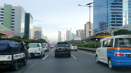 metropolitní : JAKARTA, Indonesia - May 14, 2019: Cars moving slowly on tollway at rush hour with skyscrapers view