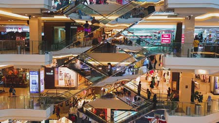consumismo : JAKARTA, Indonesia - May 14, 2019: Escalator in luxury shopping mall with crowded visitor and fashion stores view. Vídeos