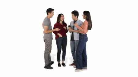 fulllength : Group of cheerful young people chatting together while using mobile phone and standing in the studio, isolated on white background. Shot in 4k resolution