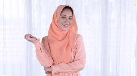 malajské : Sweet young muslim woman posing at home while wearing islamic clothes. Shot in 4k resolution