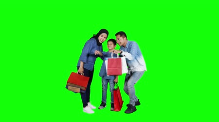 fulllength : Happy young parents and their son holding shopping bags and looking at something in the studio. Shot in 4k resolution with green screen background Stock Footage
