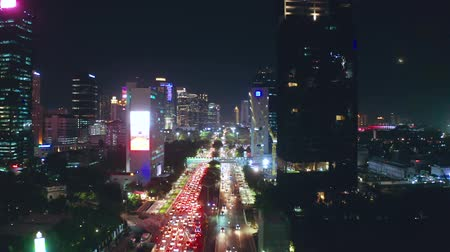 reçel : JAKARTA, Indonesia - May 13, 2019: Beautiful aerial scenery of roadway with night traffic and skyscrapers background. Shot in 4k resolution from a drone flying forwards