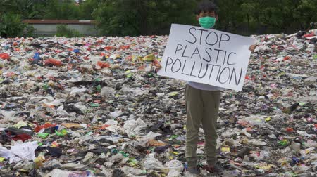 plastics : JAKARTA, Indonesia - May 21, 2019: Boy showing a banner with text of Stop Plastic Pollution on the landfill. Shot in 4k resolution