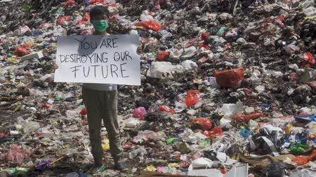 plastics : JAKARTA, Indonesia - May 21, 2019: Preteen boy standing on the landfill while holding a banner with a text of You Are Destroying Our Future. Shot in 4k resolution Stock Footage