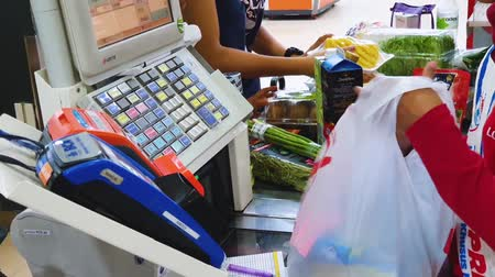 szemléltető : JAKARTA, Indonesia - May 21, 2019: Closeup of cashier hand counting the buyer groceries on the cashier machine in supermarket Stock mozgókép