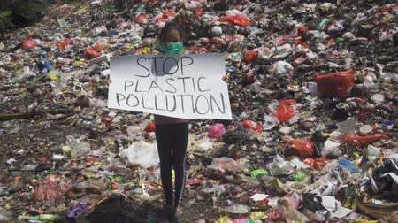 tutmak : JAKARTA, Indonesia - May 21, 2019: Little girl showing a banner with text of Stop Plastic Pollution while standing on the landfill at Earth Day. Shot in 4k resolution