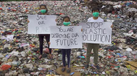 plastics : JAKARTA, Indonesia - May 21, 2019: People standing on the landfill while showing banner with text of Save Our Planet, Stop Plastic Pollution, and You Are Destroying Our Future. Shot in 4k resolution