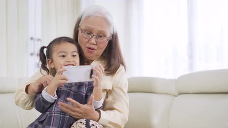 indonesian : Happy little girl and her grandmother using a smartphone while sitting on the sofa at home. Shot in 4k resolution