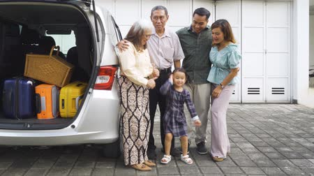 bavul : Happy little girl standing with her parents and grandparents beside the car with luggage for traveling. Shot in 4k resolution Stok Video