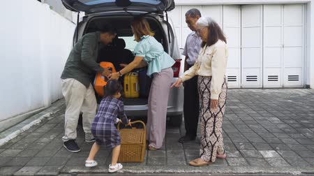 bavul : Cute little girl helping her parents to load luggage into the car trunk for traveling. Shot in 4k resolution Stok Video